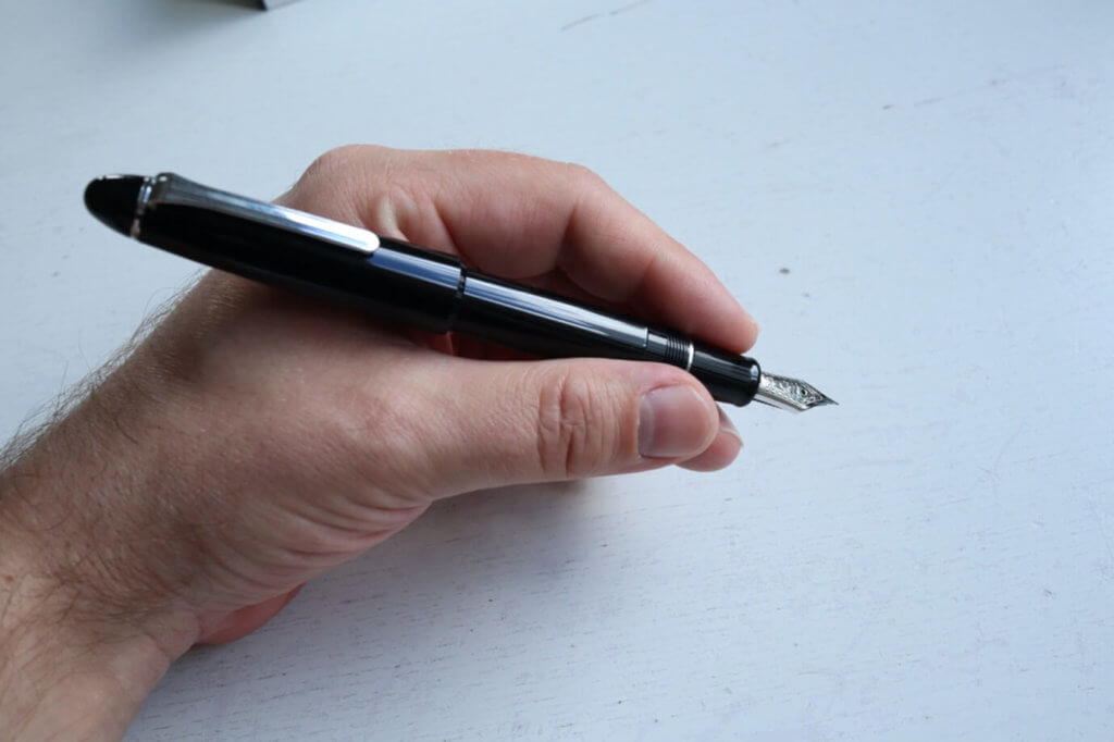A posted Sailor 1911 Ringless fountain pen in Simply Black being held in a hand