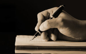 A hand writing with a fountain pen into a book.