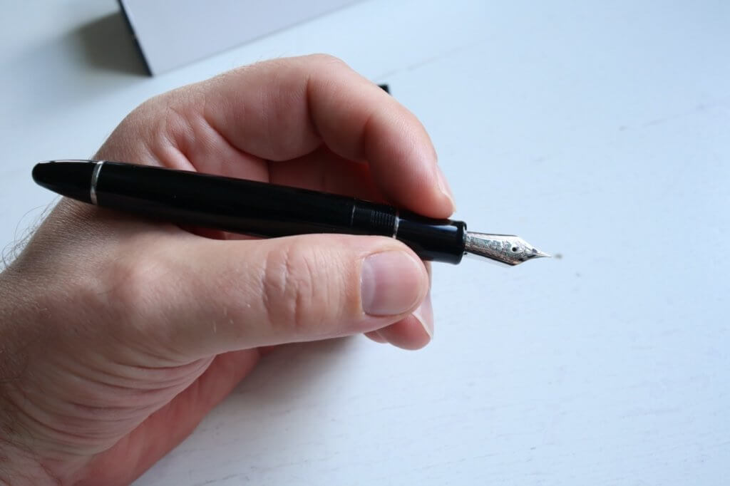 An unposted Sailor 1911 Ringless fountain pen in Simply Black, being held in a hand