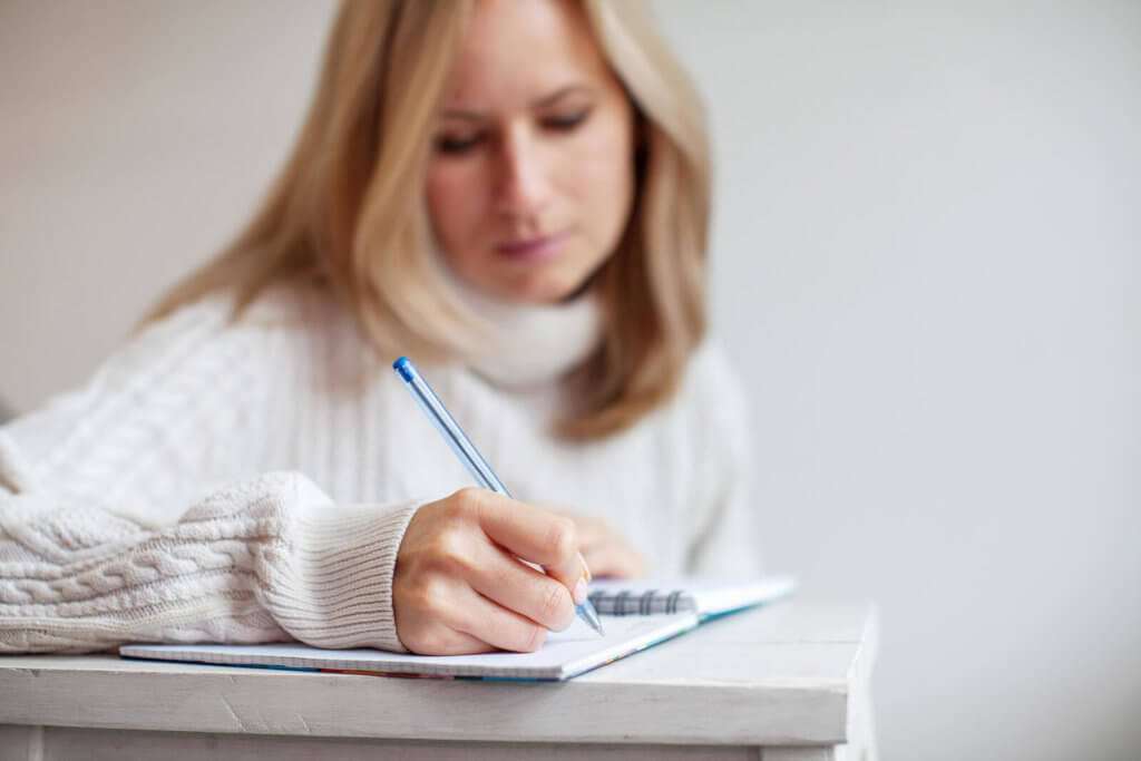 A blonde woman writing with a pen in a notebook