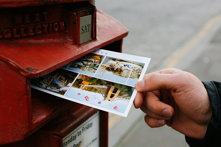 Mailing a postcard in a postbox
