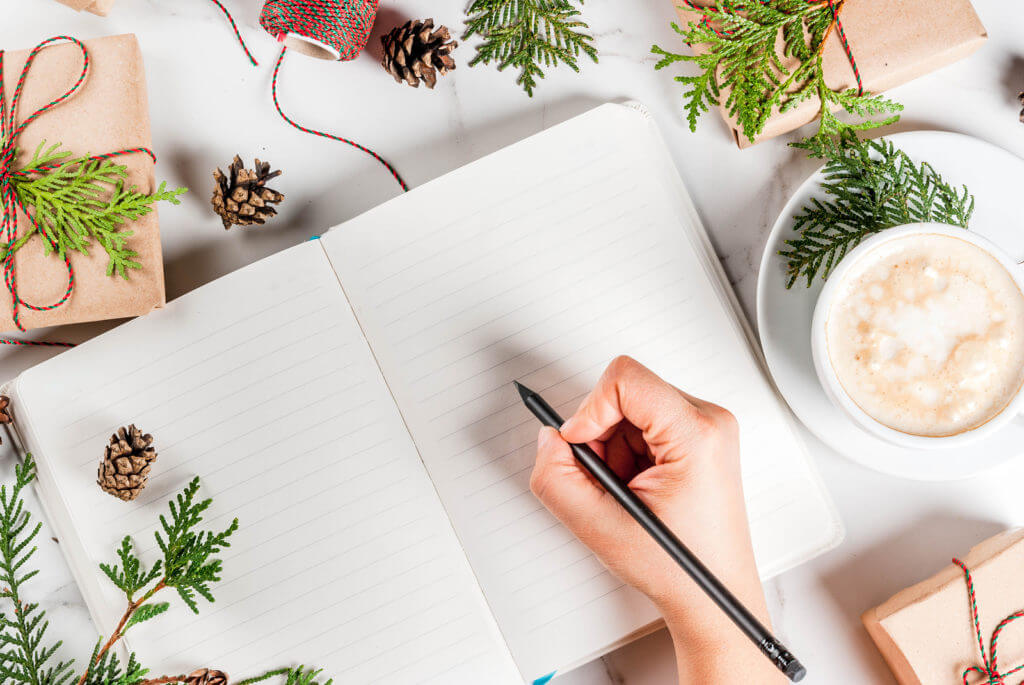 Woman writing in Christmas journal