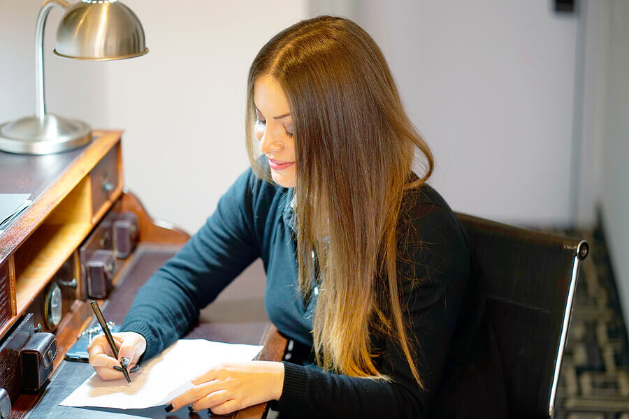 woman writing letter sat at desk
