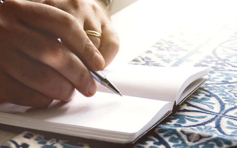 a man's hand writing in a book with a pen