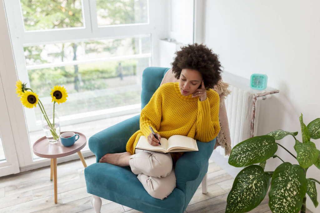 a woman writing in a book while sat down in a blue chair
