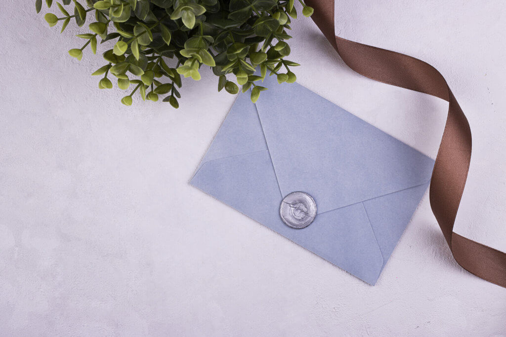 A blue envelope featuring a silver wax seal