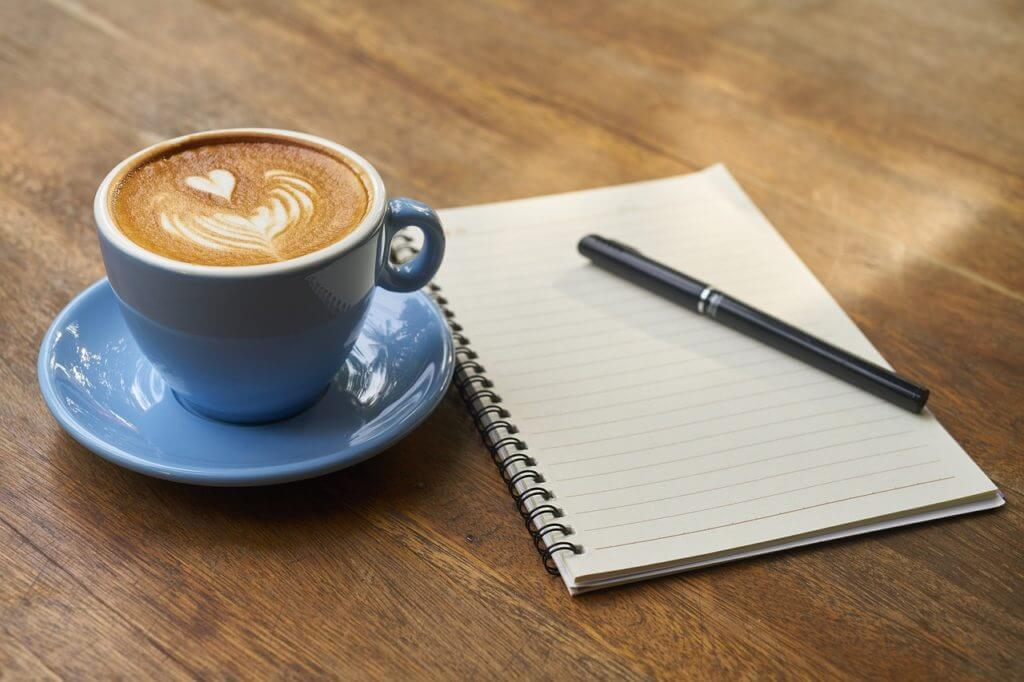 pen, notepad and coffee cup