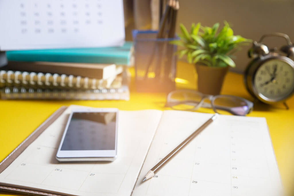 A diary, pencil and mobile phone on a desk