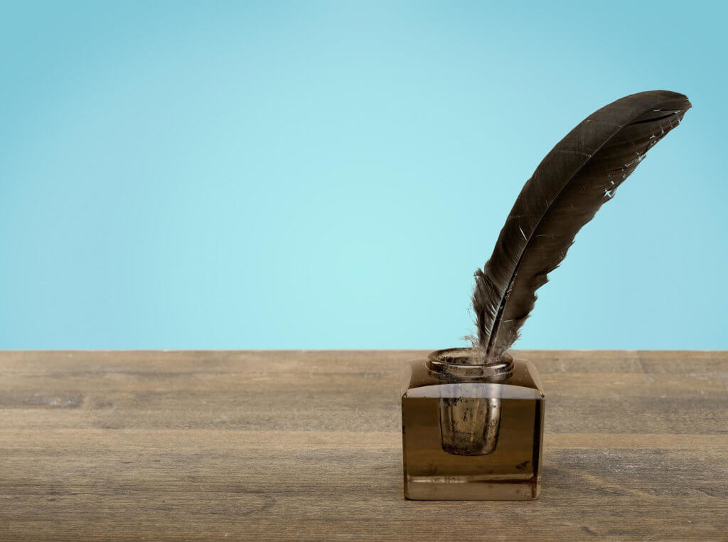A feather quill pen resting in an inkwell on a wooden table, with a blue background