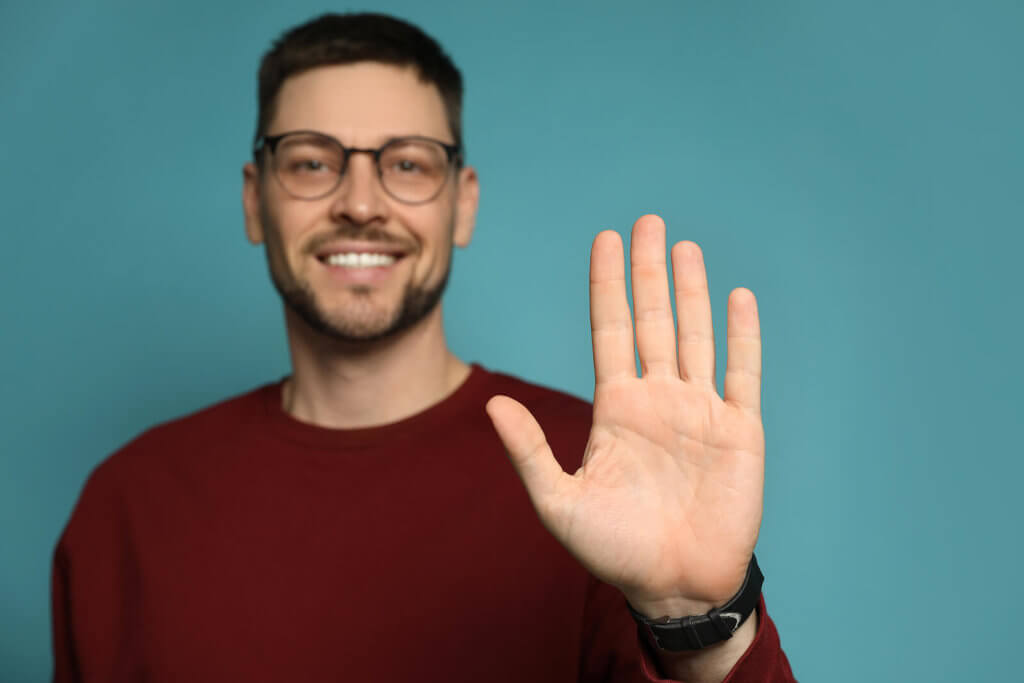 A man in a red jumper stood against a blue background, holding his left hand up and forwards toward the camera, representing left-handedness