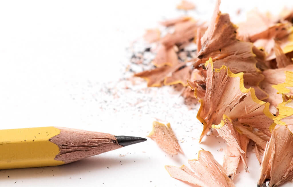 A freshly sharpened yellow wooden pencil with pencil shavings, on a white background