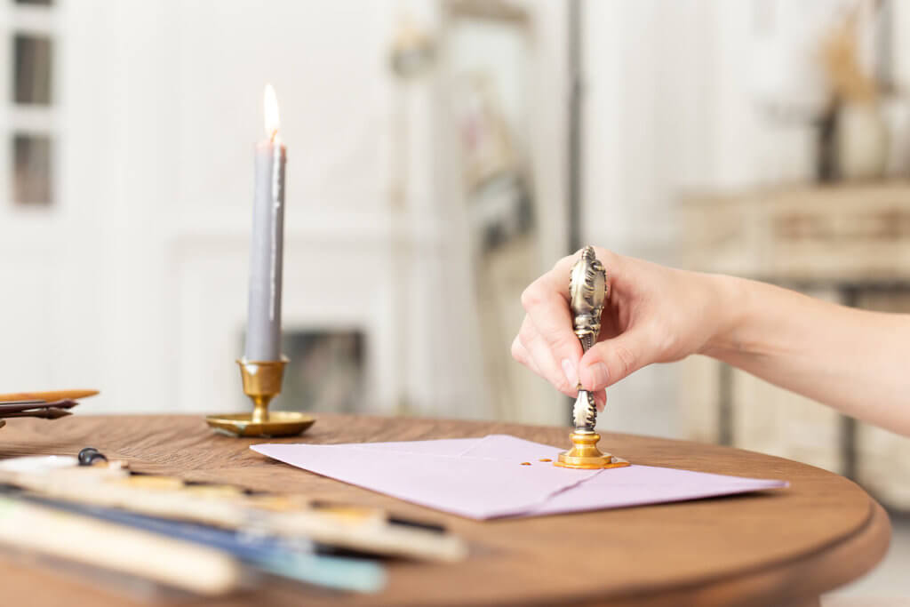 A hand stamping a wax seal on an envelope