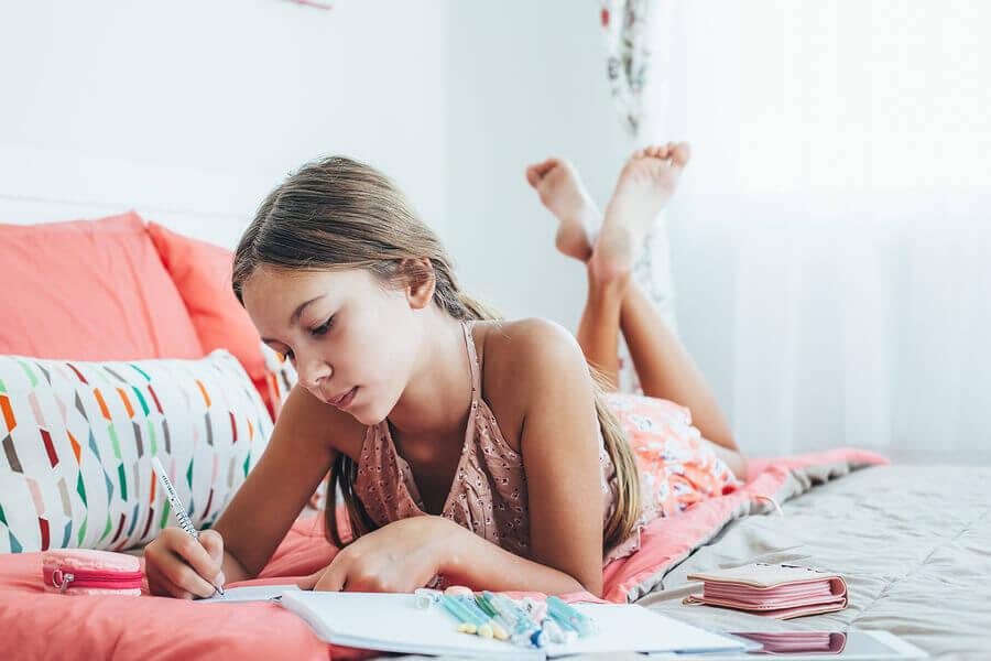 writing tween girl on bed
