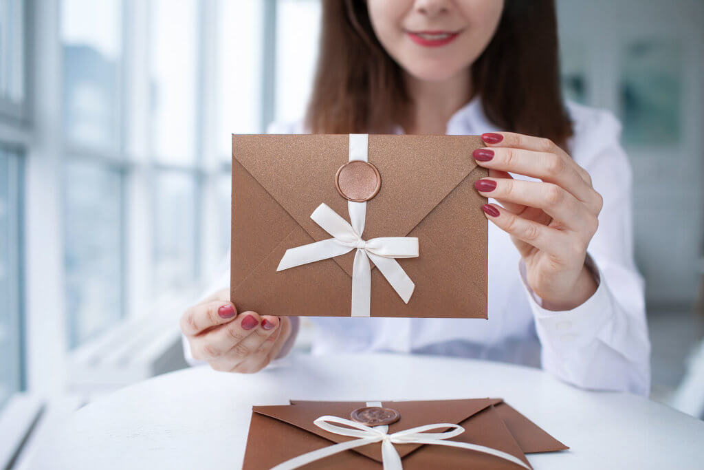 A woman holding a manilla envelope that features a ribbon and wax seal