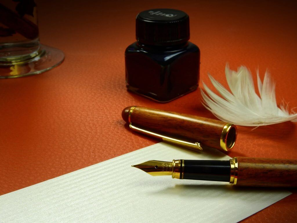 Fountain pen, bottle of ink and a feather