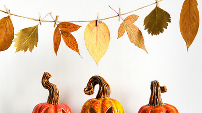 A row of three carved ceramic pumpkins with tealights, underneath a leaf garland — representing autumn and Halloween.